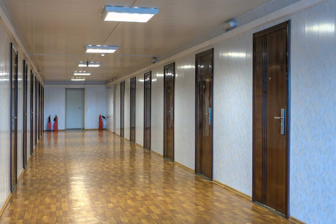 Long,Office,Hallway,With,Many,Doors,Of,Dark,Red,Wood.
